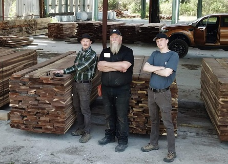 Three men standing next to stacks of boards made of walnut for Loggers Sangamon County IL